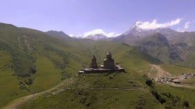 Silhueta do homem de negócio Cowering A igreja de Gergeti no fundo de Kazbek vídeos de arquivo
