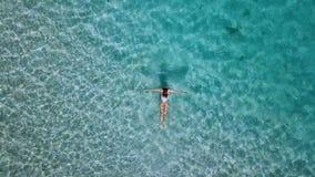Silhueta do homem de negócio Cowering Jovem mulher bonita no biquini branco que flutua na superfície da água no oceano claro da c vídeos de arquivo