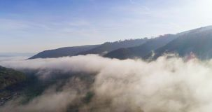 Silhueta do homem de negócio Cowering Voo sobre as montanhas altas em nuvens bonitas Tiro da câmera aérea Areje nuvens filme
