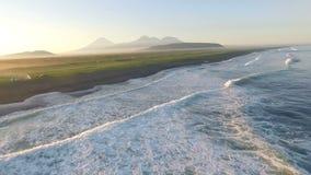 Silhueta do homem de negócio Cowering Voo sobre o mar durante o por do sol Montanhas na névoa no fundo filme