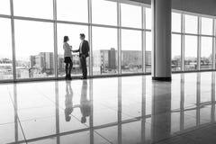 Silhueta do homem de negócios e da mulher de negócios que agitam as mãos no escritório com as janelas panorâmicos grandes Imagem de Stock