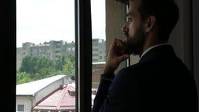 Silhueta do homem de negócios farpado novo em seu escritório que olha através da janela video estoque