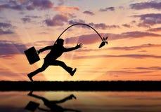 Silhueta do homem de negócios que corre para a cenoura e a reflexão na água Fotos de Stock