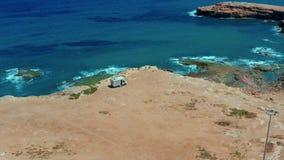 Silhueta do homem de neg?cio Cowering Camionete de campista em um parque de estacionamento em uma rocha perto do mar Parque do rv vídeos de arquivo