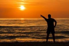 Silhueta do homem do nascer do sol que indica Sun Foto de Stock