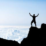 Silhueta do homem do sucesso, escalando nas montanhas Foto de Stock Royalty Free