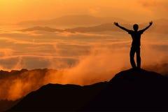 A silhueta do homem do turista espalhou a mão sobre uma montanha aprecia Foto de Stock