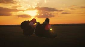A silhueta do homem dois na parte superior da montanha com trouxas e da outra engrenagem que expressa a energia e a felicidade Do filme