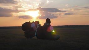 A silhueta do homem dois na parte superior da montanha com trouxas e da outra engrenagem que expressa a energia e a felicidade Do vídeos de arquivo