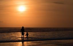 Silhueta do homem e da criança unrecognisable no beira-mar Imagem de Stock Royalty Free