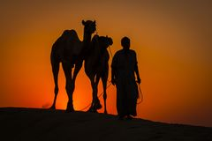 A silhueta do homem e dois camelos no por do sol em Thar abandonam perto de Jaisalmer, Rajasthan, Índia Fotografia de Stock Royalty Free