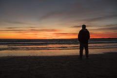 Silhueta do homem em um por do sol bonito na praia Fotografia de Stock