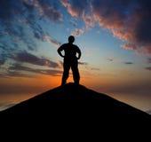 Silhueta do homem em uma parte superior da montanha Fotografia de Stock