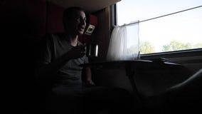 A silhueta do homem está sentando-se em um trem Railway do transporte na janela de um compartimento que o carro está bebendo o ch filme