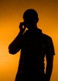 A silhueta do homem fala sobre o telefone Fotografia de Stock Royalty Free