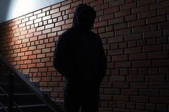 Silhueta do homem misterioso no hoodie Criminoso perigoso imagem de stock