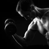 Silhueta do homem muscular novo da aptidão no preto Fotos de Stock Royalty Free