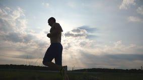 Silhueta do homem muscular que movimenta-se na estrada secundária no por do sol Treinamento masculino do basculador para exterior video estoque