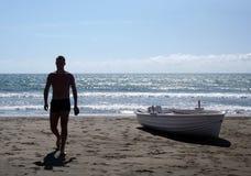 Silhueta do homem novo que anda em uma praia Fotos de Stock