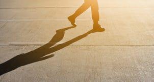 Silhueta do homem que anda ou que pisa com sombra e luz solar fotos de stock royalty free