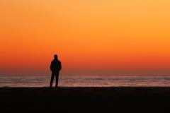 Silhueta do homem que está pelo oceano Imagem de Stock