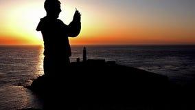 Silhueta do homem que faz fotos com o smartphone durante o por do sol no farol sul da pilha - Anglesey, Gales video estoque