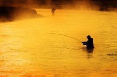 Silhueta do homem que Flyfishing no rio Fotografia de Stock