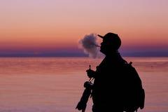 Silhueta do homem que fuma uma tubulação no tampão no por do sol fotógrafo Imagens de Stock Royalty Free