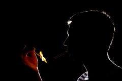 Silhueta do homem que ilumina o cigarro na obscuridade Imagens de Stock Royalty Free