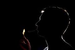 Silhueta do homem que ilumina o cigarro na obscuridade Foto de Stock Royalty Free