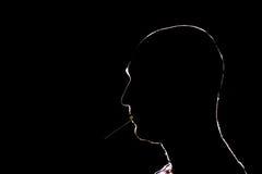 Silhueta do homem que ilumina o cigarro na obscuridade Foto de Stock