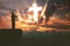 Silhueta do homem que reza ao deus com o raio de luz que dá forma à cruz imagens de stock royalty free