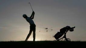 Silhueta do jogador de golfe do menino com o saco de golfe no por do sol video estoque