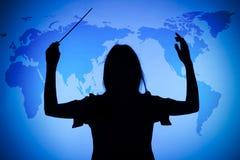 Silhueta do maestro fêmea no mapa de mundo imagens de stock royalty free