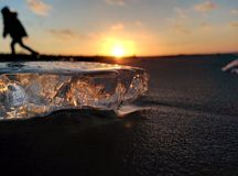 Silhueta do menino e do gelo no tempo do por do sol da costa de mar Foto de Stock