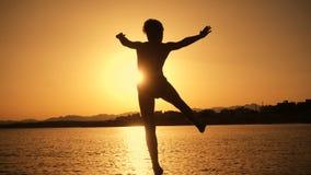 Silhueta do menino que salta do cais no por do sol no mar filme