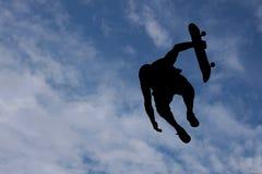 Silhueta do menino que salta com skate Imagem de Stock