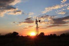 Silhueta do moinho de vento de Kansas com céu dourado Fotografia de Stock