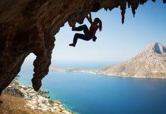 Silhueta do montanhista de rocha fêmea novo em um penhasco Fotos de Stock