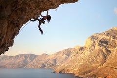 Silhueta do montanhista de rocha fêmea novo em um penhasco Imagens de Stock Royalty Free