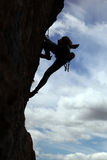 Silhueta do montanhista de rocha que escala um penhasco Fotografia de Stock