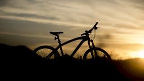Silhueta do Mountain bike com luz do por do sol Fotos de Stock Royalty Free