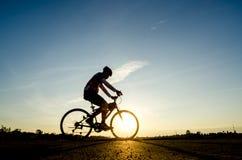 Silhueta do movimento do ciclista no fundo do por do sol Imagens de Stock