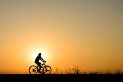 Silhueta do movimento do ciclista no fundo do por do sol Fotografia de Stock