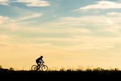 Silhueta do movimento do ciclista no fundo do por do sol Imagem de Stock Royalty Free