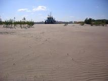 A silhueta do navio contra o deserto arenoso é vista na distância imagens de stock