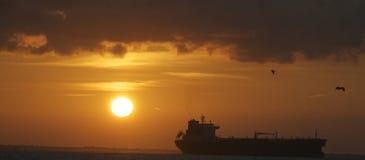 Silhueta do navio contra o por do sol vibrante Fotos de Stock Royalty Free