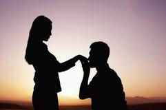 Silhueta do noivo que ajoelha-se e que beija sua mão das amigas no por do sol fotos de stock