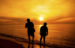 A silhueta do pai e do filho tomou uma caminhada na praia Imagens de Stock
