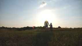 Silhueta do pai e do filho que andam no campo no por do sol e que guardam as mãos de se Família feliz que passa o tempo filme